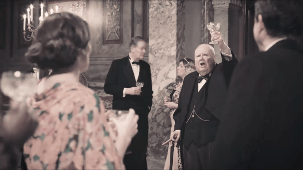 An actor dressed as Winston Churchill raises a glass to toast at a party.