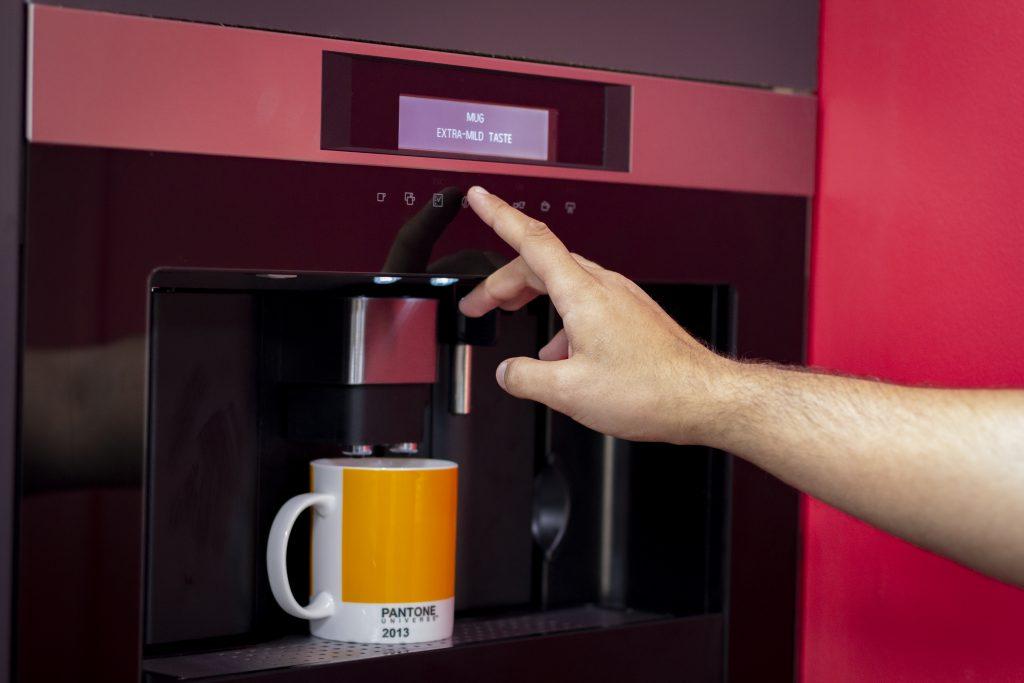 Hand operating coffee machine with yellow mug